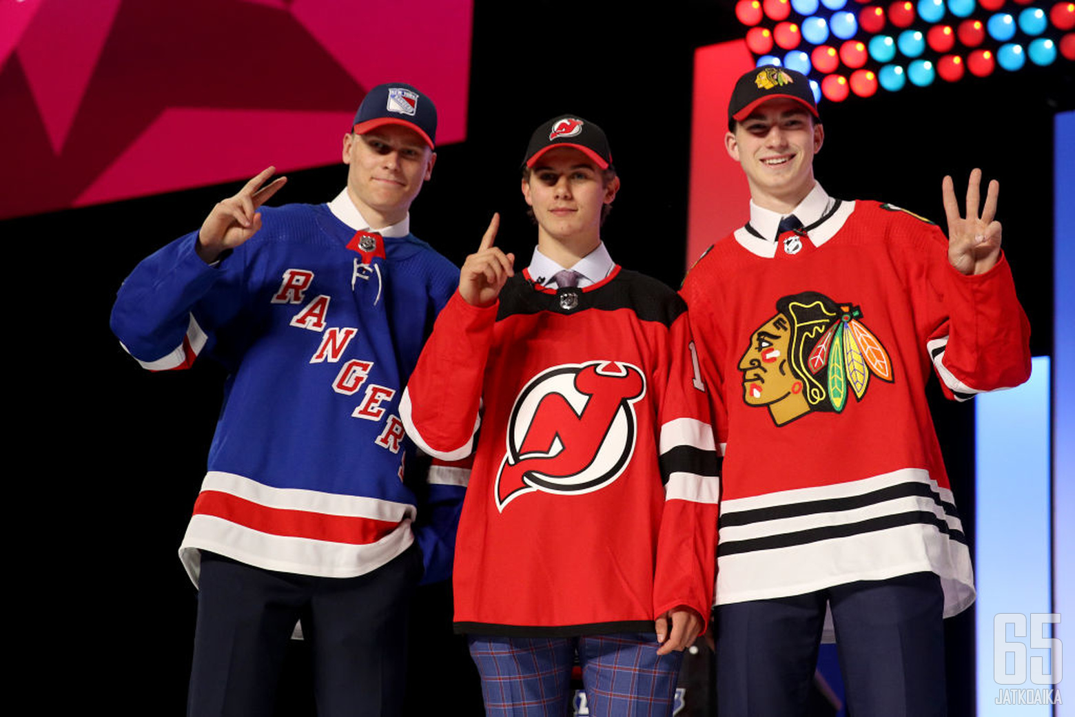 VANCOUVER, BRITISH COLUMBIA - JUNE 21:  (L-R) Kaapo Kakko, second overall pick by the New York Rangers, Jack Hughes, first overall pick by the New Jersey Devils, and Kirby Dach, third overall pick by the Chicago Blackhawks hold up their fingers of their p