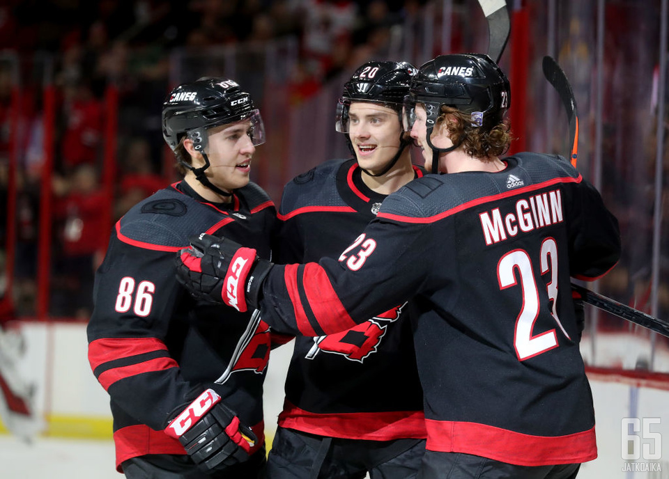 RALEIGH, NC - JANUARY 13:  Sebastian Aho #20 of the Carolina Hurricanes celebrates with teammates Teuvo Teravainen #86 and Brock McGinn #23 after scoring a goal during an NHL game against the Nashville Predators on January 13 ,2019 at PNC Arena in Raleigh