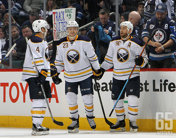 WINNIPEG, MB - JANUARY 10: Josh Gorges #4, Sam Reinhart #23 and Ryan O'Reilly #90 of the Buffalo Sabres celebrate Reinhart's hat trick goal against the Winnipeg Jets at the MTS Centre on January 10, 2016 in Winnipeg, Manitoba, Canada. (Photo by Jonathan K