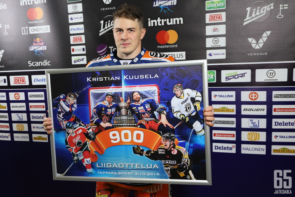 Kapteeni Kristian Kuusela esitteli Sport-ottelun jälkeen ylpeänä joukkueelta saamaansa taulua.