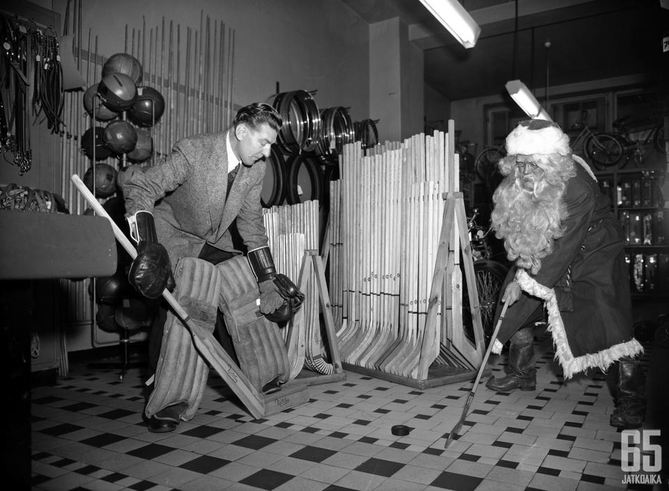 Joulupukki harjoittelee jääkiekkoa kauppakeskuksessa. Kuva on Helsingin kaupunginmuseon arkistosta.