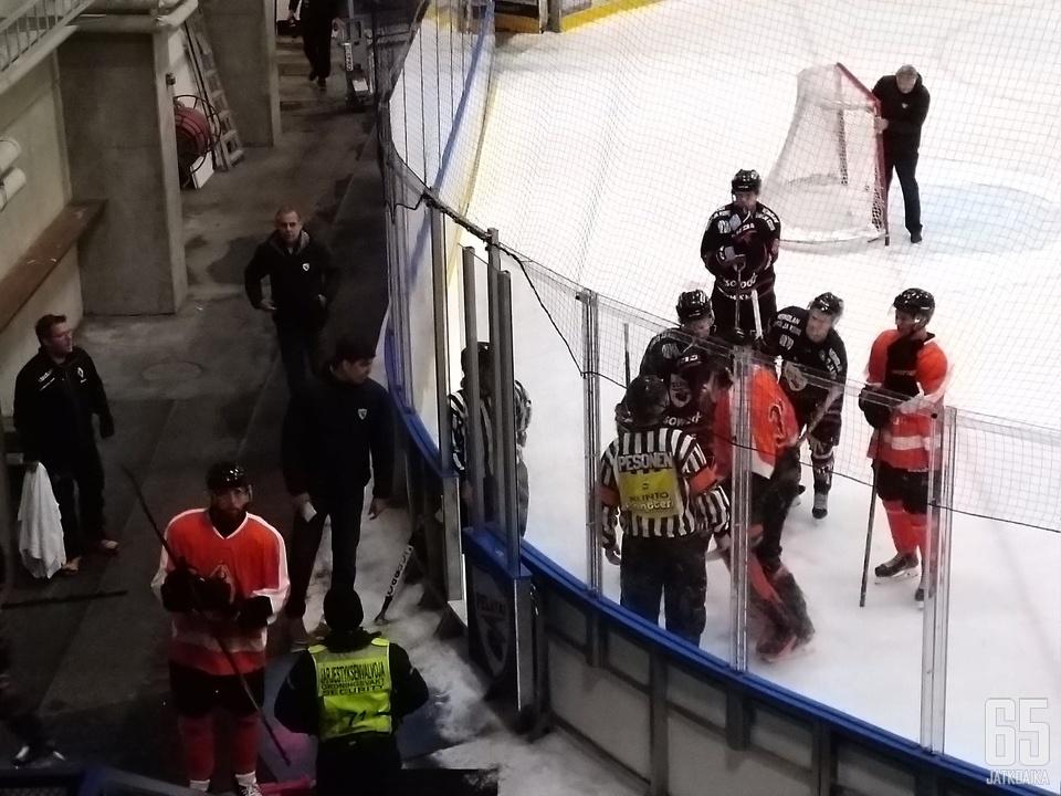 Tuomarit joutuivat suorittamaan poroerottelua joukkueiden poistuessa pukukoppiin. Taustalla säestää suihkukomennuksen saanut Peliittojen päävalmentaja Vesa Petäjä.
